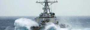 Navy ship crashing through waves at sea