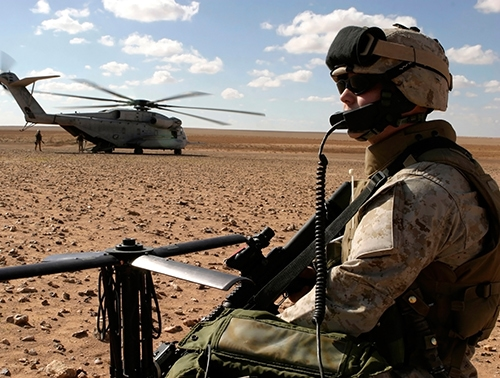Military Satcom - soldier stands in desert with helicopter in background